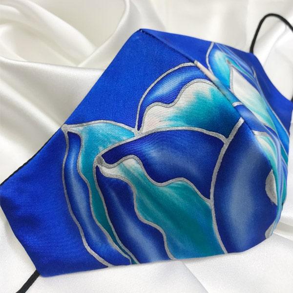 Mascarilla homologada de seda pintada a mano con flor salvaje azul y jade sobre fondo azul eléctrico.