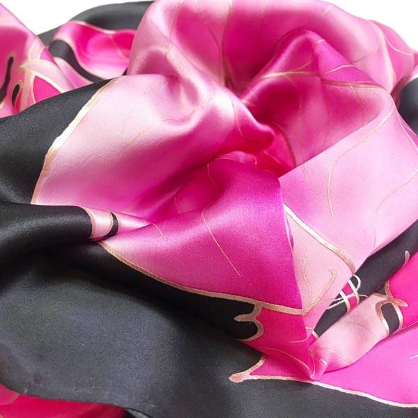 Fular de seda pintado a mano con hojas rosas y fondo negro.